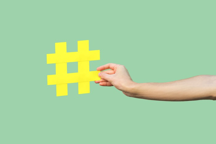A hand holds a yellow hashtag symbol