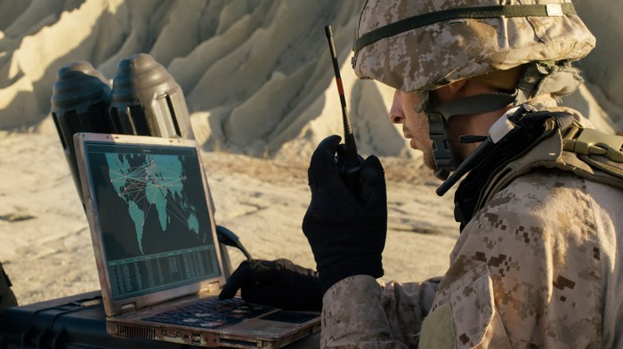 A soldier using a rugged laptop computer during military operation in the desert.