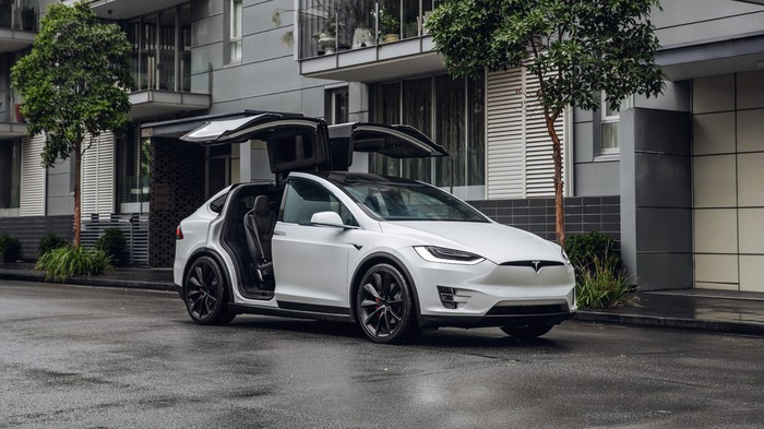 A white Model X with its falcon wing doors open