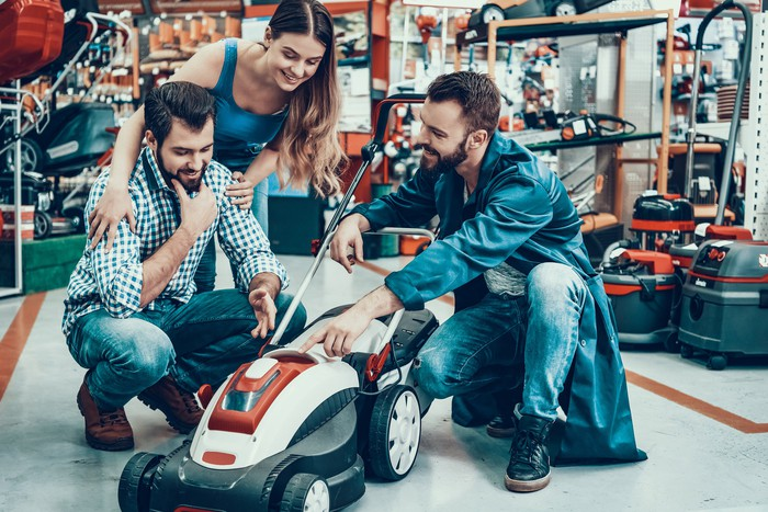 People looking at a lawn mower in a retail store