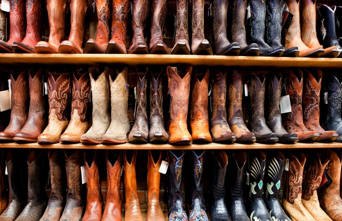 Rows of cowboy boots on a store's shelves.