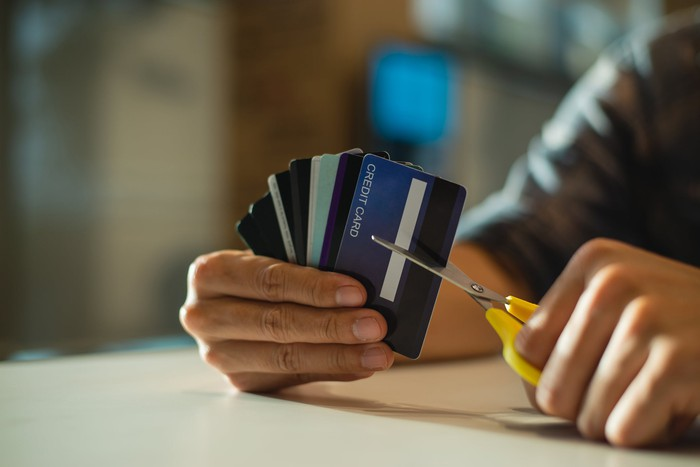 Hands holding scissors and cutting up an entire stack of credit cards