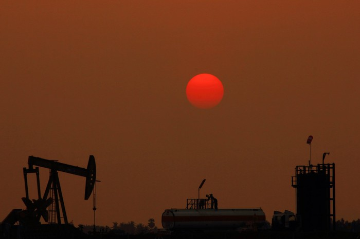A red moon above an oil pump and midstream infrastructure.