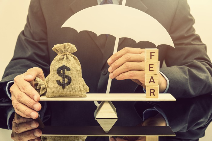 A man holds a cutout of an umbrella behind a balance scale, with a sack of money on one side and wooden blocks spelling FEAR on the other side