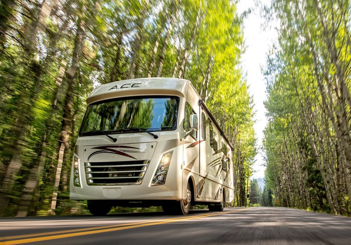A Thor Class A motorhome drives on a road through a clearing of trees..