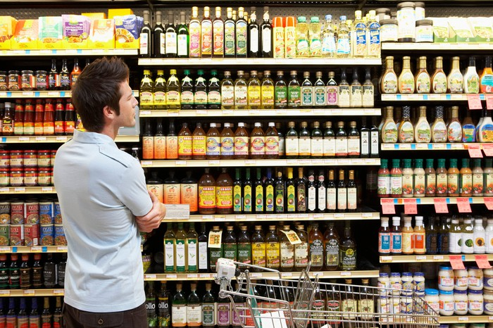 Man looking at sauces, oils, and salad dressing in a grocery store aisle.