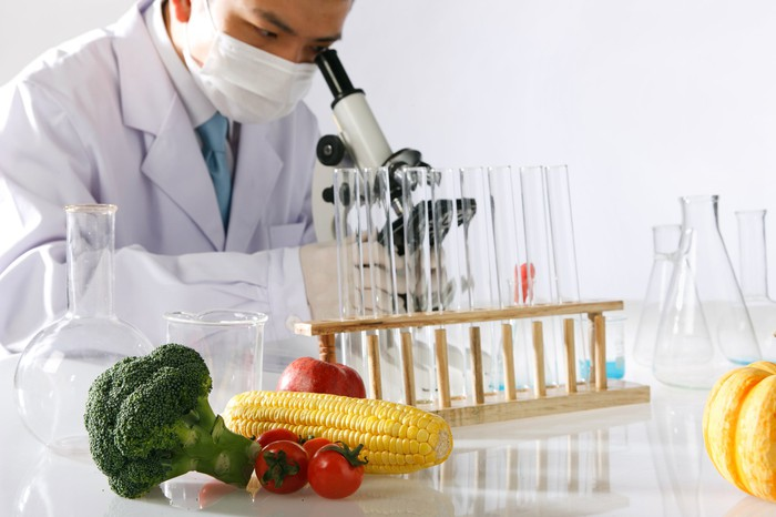 A scientist looking into a microscope with test tubes and some vegetables in the foreground.