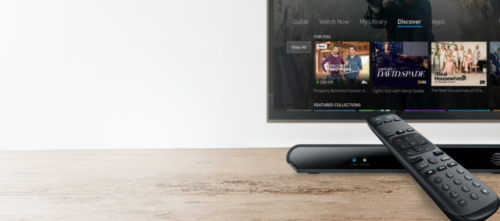 The AT&T TV set-top box and remote on a table, and the homescreen displayed on a television.
