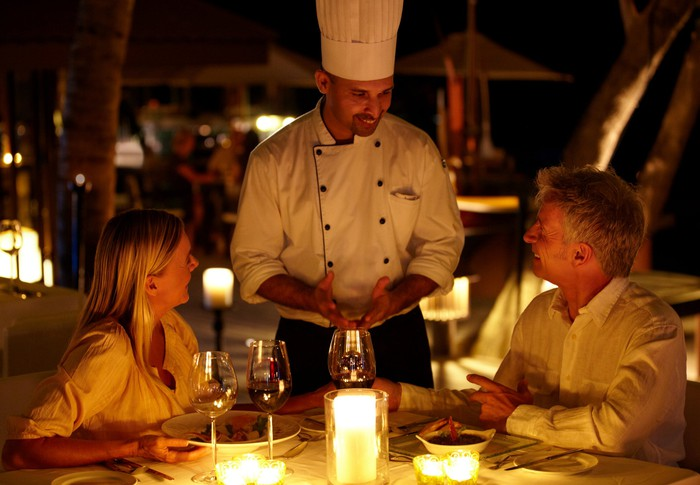 A chef serving two customers at a restaurant