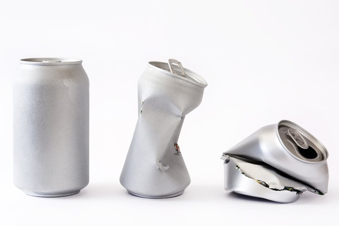 An aluminum can, a partially crushed aluminum can, and a fully crushed aluminum can.