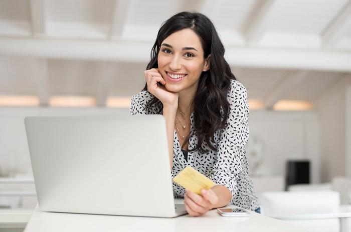 A smiling woman holding a credit card in her left hand, with her open laptop in front of her.