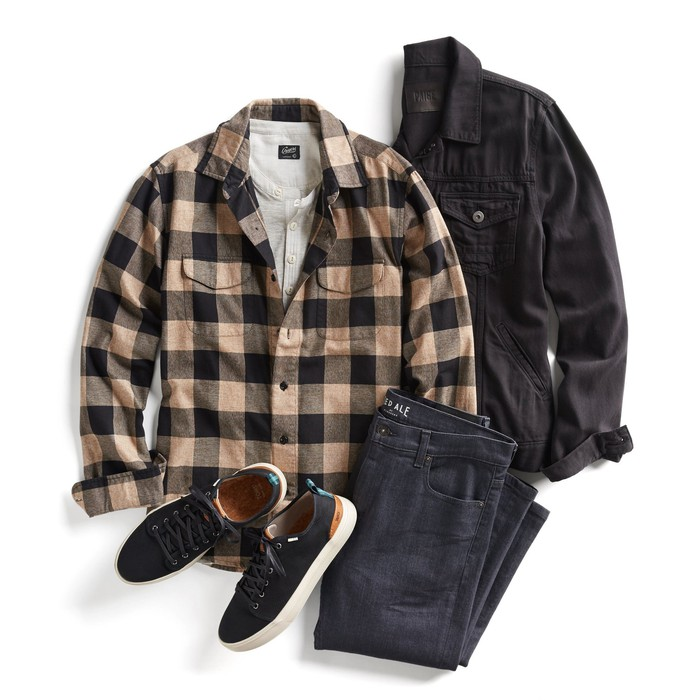 Various men's pieces -- black jeans, black jeans jacket, tan-and-brown checked flannel shirt over a white shirt, and a pair of black sneakers.