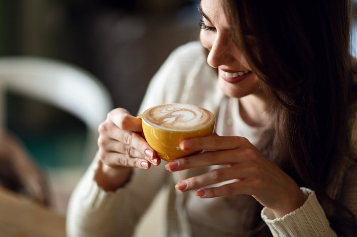 A woman holds a latte in a mug.