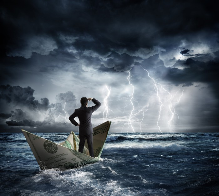 A businessman in a paper money boat staring out at a stormy sea.