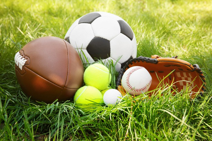 Various balls and a baseball glove in the grass