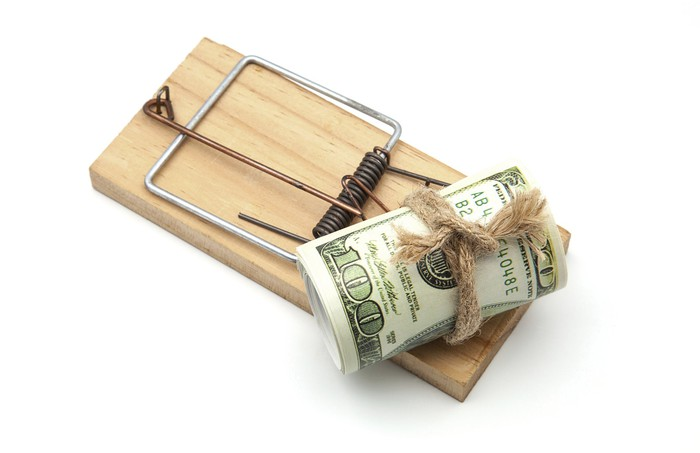 Wood mousetrap with roll of $100 bills as bait.