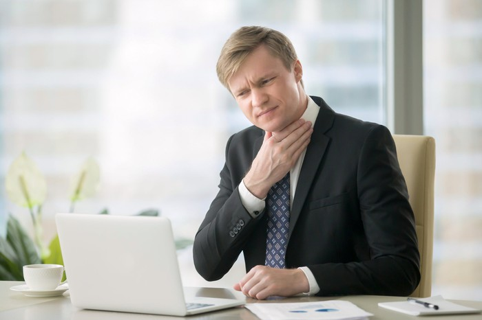 Man in suit at desk touching his neck