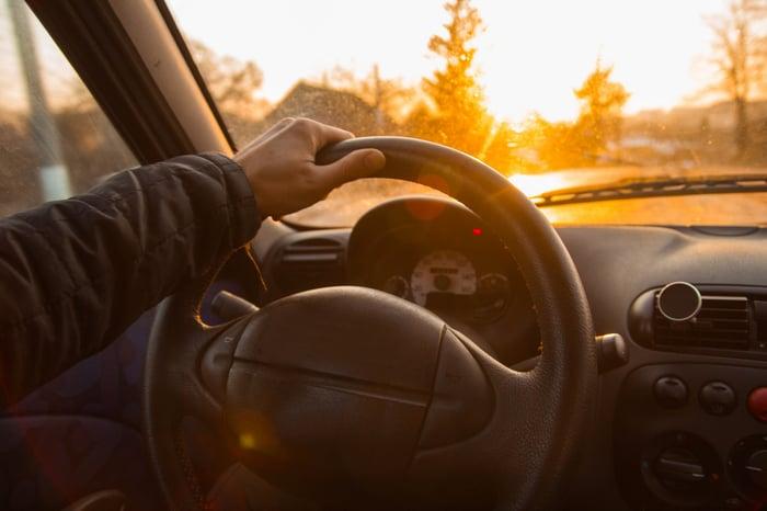 Man steering a car as sun sets