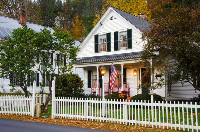 A modest white single family home with a white picket fence