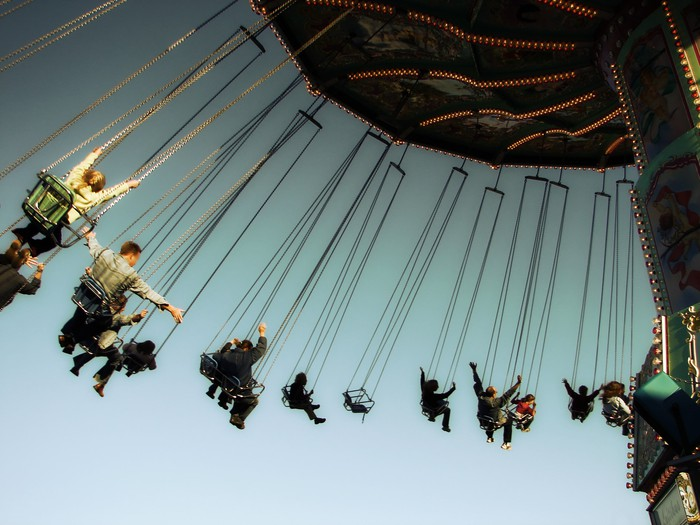Visitors at a theme park on a swinging ride.