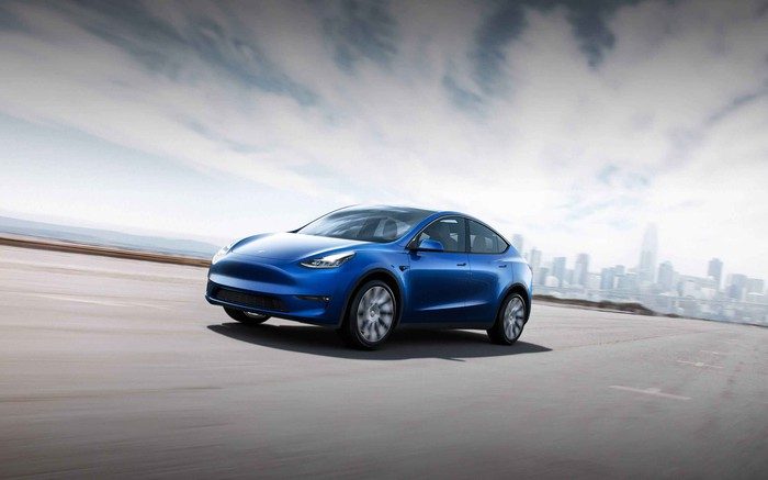 A blue Tesla Model Y moving down a road with a city skyline in the background.