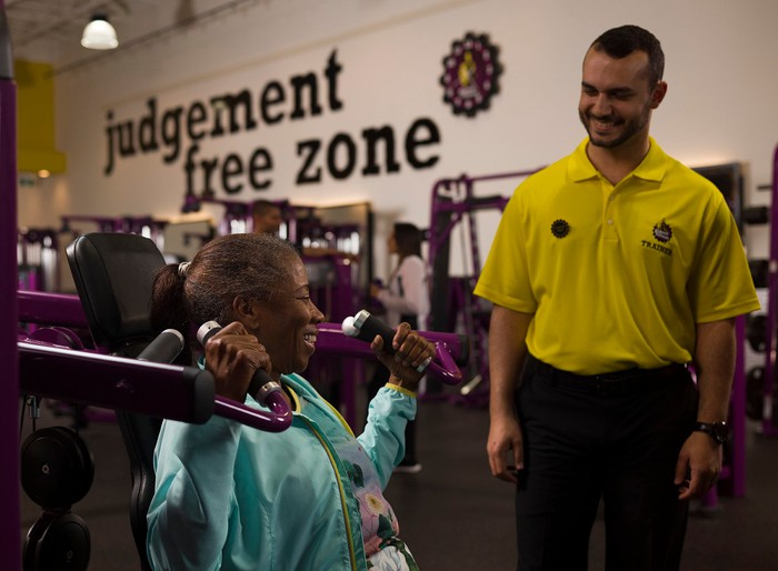 A Planet Fitness trainer smiles at a woman who is working out.