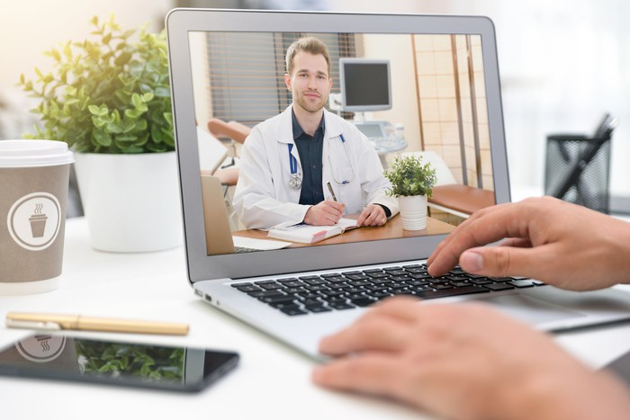 A person speaking to a doctor via videoconferencing technology on a tablet computer.