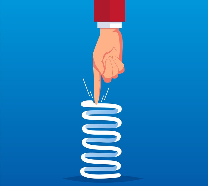 Cartoon-style drawing of a hand pushing down on a compressed spring coil.