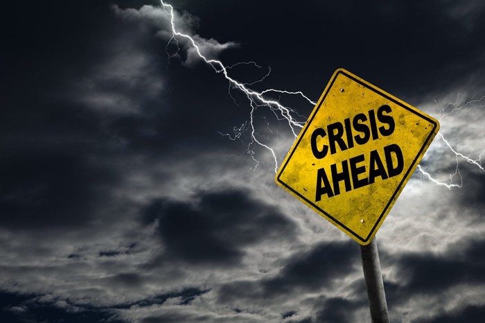 A road sign that says crisis ahead is shown, against a darkened sky with lightning.