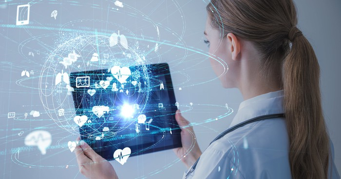 Female healthcare professional holding tablet with images of organs
