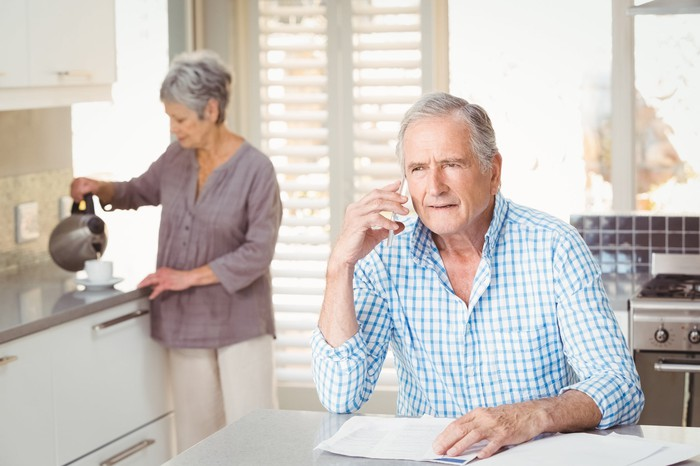 Older man holds phone to ear while older woman pours from kettle in the background