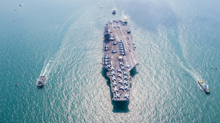 Stock photo of a aircraft carrier with support ships.