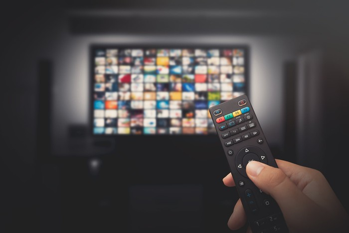 A person's hand holding a television remote in front of a television with lots of choices on the screen.