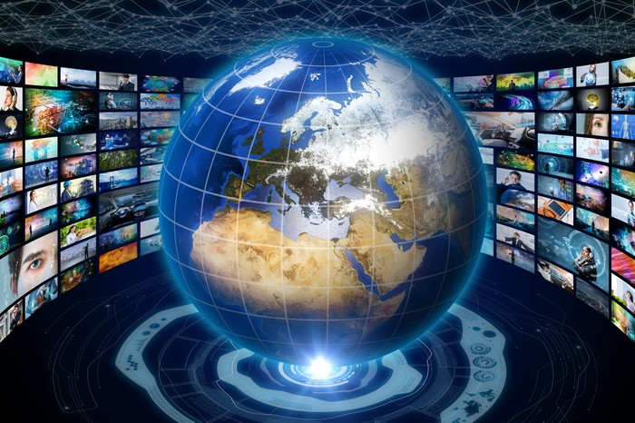 A floating globe surrounded by various television screens.
