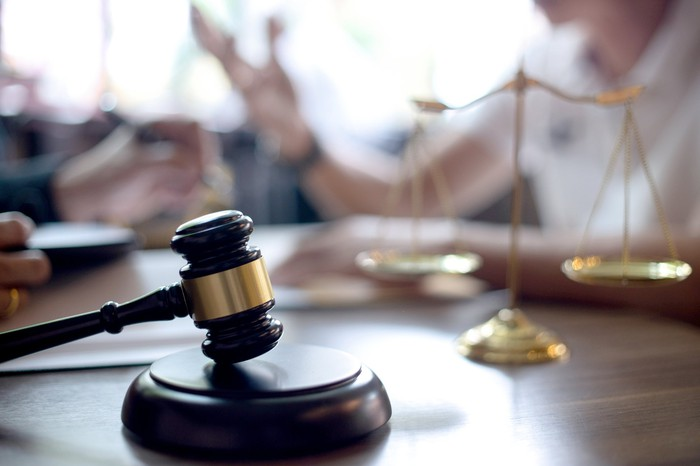 A gavel and scales of justice sit on a desk.