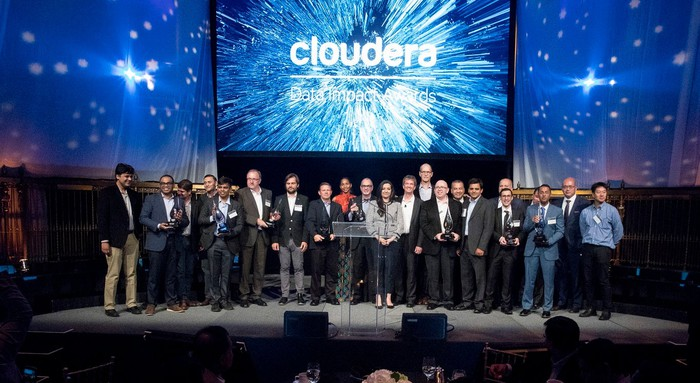 A couple dozen people on a stage in front of a screen with Cloudera's logo on it.