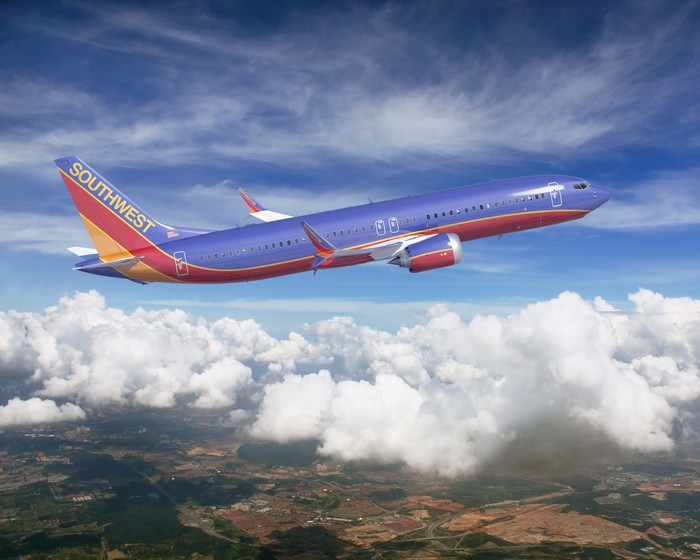 A Southwest Airlines branded Boeing 737 MAX flies over a rural landscape.