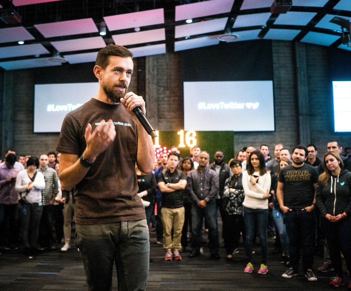 Jack Dorsey holding a microphone in front of a crowd.