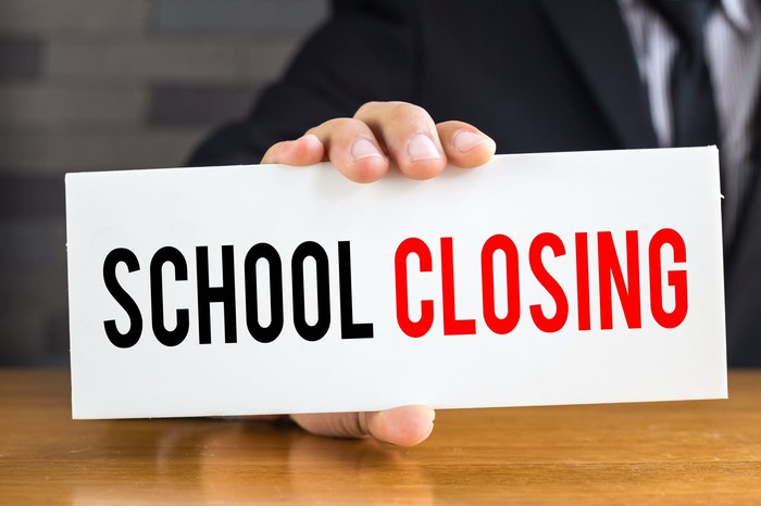 School closing, message on white card and hold by businessman