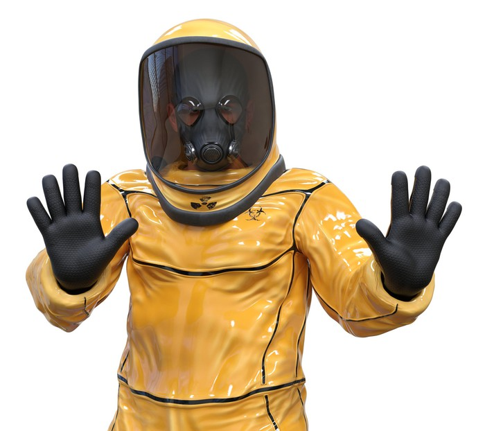 Man in yellow biohazard suit making a stop gesture with his hands
