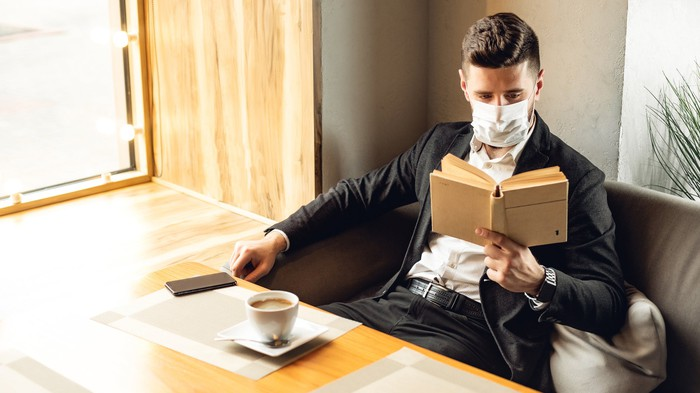 Man reading in a coffee shop wearing a face mask