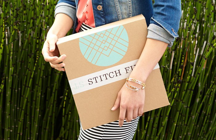 A woman is holding a package with the Stitch Fix logo.