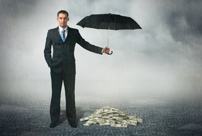 A man in a suit holds an umbrella over a pile of money during a storm.
