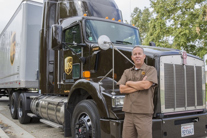 A UPS truck driver posing next to his rig.