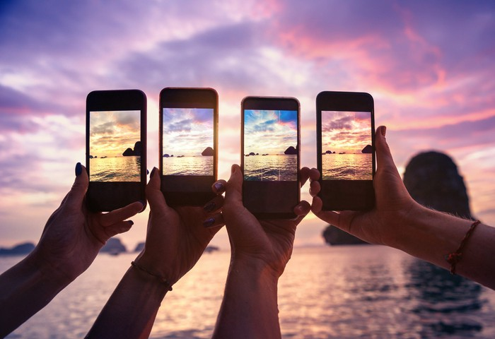 Four smartphones being use to take pictures of a coast.