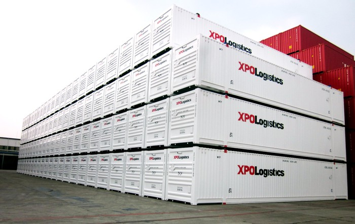 A stack of XPO-branded containers sits at a port.