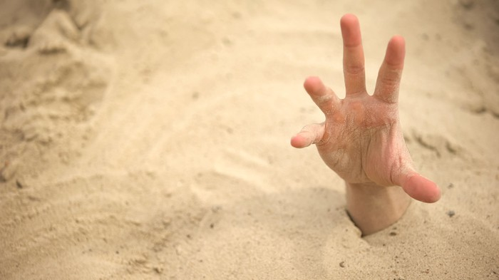 Hand sticking out of sand