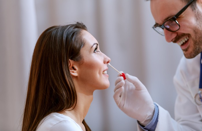 Doctor swabbing a woman's nose