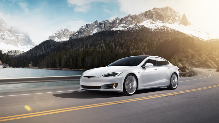 A white Model S on the road. Mountains are in the background.