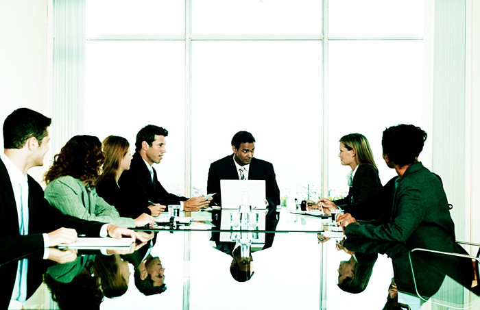 Office workers meet around a long boardroom table.